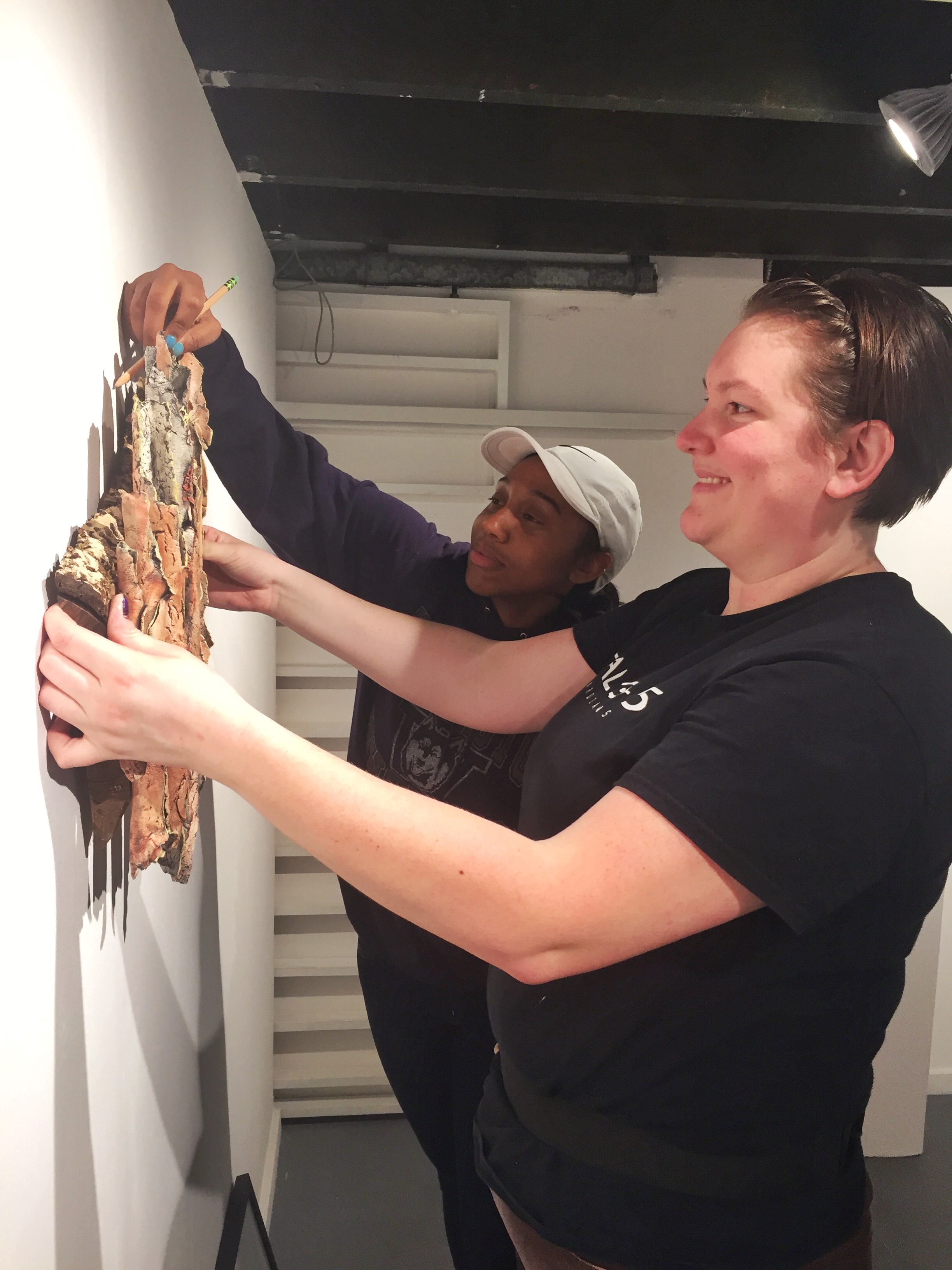 Exhibitions Program Manager Colleen Lenahan and Intern install gallery exhibit